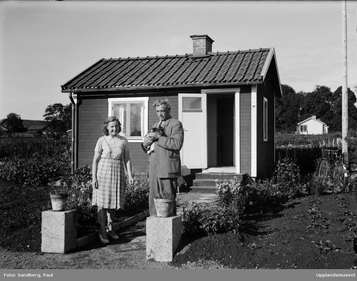 Tunabergs koloniträdgårdsförenings ordförande, ombudsman Karl Axel Åberg med fru Lagerkvist framför hennes kolonistuga i Tunabergskolonin, Tuna backar